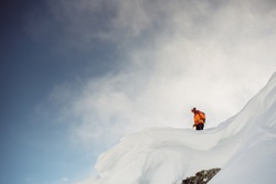 Male skiier standing on top of cliff in the alps looking down at slope before dropping in