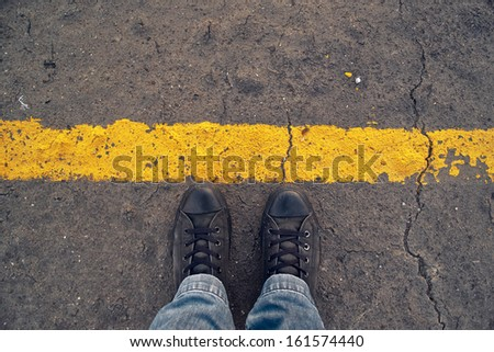 Male sneakers on the asphalt road behind yellow line. Border line concept, danger or warning sign at the frontier. - stock photo