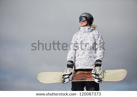 male snowboarder against sun and blue sky