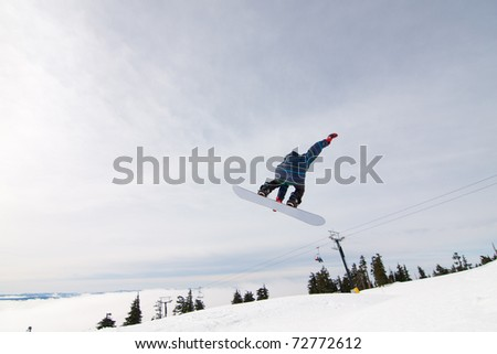 Male Snowboarder Catches Big Air on a Bright Sunny Day.