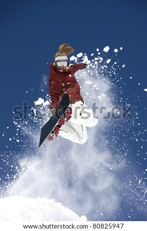 Male snowboarder in mid-air making extreme jump.