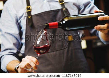 Male sommelier pouring red wine into long-stemmed wineglasses. #1187165014