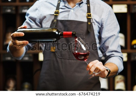 Male sommelier pouring red wine into long-stemmed wineglasses. Stock photo ©