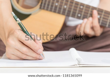 male songwriter hands writing a song on paper while playing acoustic guitar. song writing concept