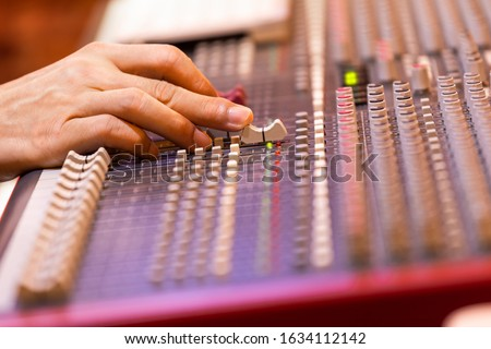 male sound engineer, dj hand working on audio mixing console. music production, post production, broadcasting concept