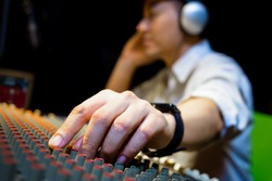 male sound engineer hands working on audio mixing console in recording, broadcasting studio