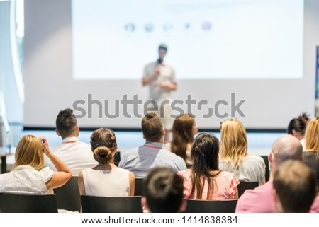 Male speaker giving a talk in conference hall at business event. Audience at the conference hall. Business and Entrepreneurship concept. Focus on unrecognizable people in audience.