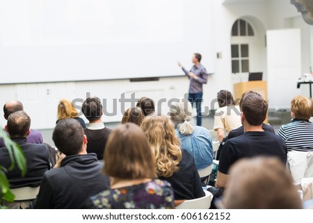 Male speaker giving presentation in lecture hall at university workshop. Audience in conference hall. Rear view of unrecognized participant. Scientific conference event. Copy space on whitescreen.