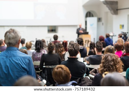 Male speaker giving presentation in lecture hall at university workshop. Audience in conference hall. Rear view of unrecognized participant in audience. Scientific conference event. #757189432