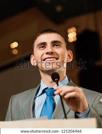 male speaker looks into the room and said into the microphone, speech at the conference