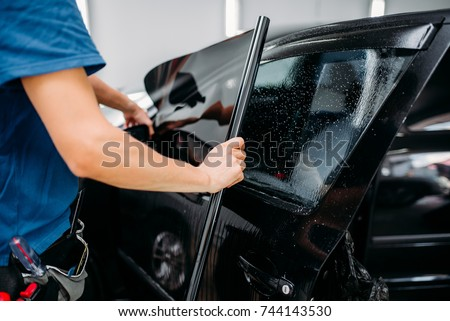Male specialist applying car tinting film