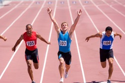 Male sprinter raising his arms in victory with his colleagues behind him on a bright, sunny day at the track