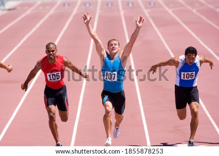 Male sprinter raising his arms in victory with his colleagues behind him on a bright, sunny day at the track Stok fotoğraf ©