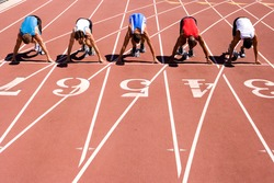 Male sprinters waiting for the start of a sprint race on their starting blocks behind lane markings at an athletics event on the track