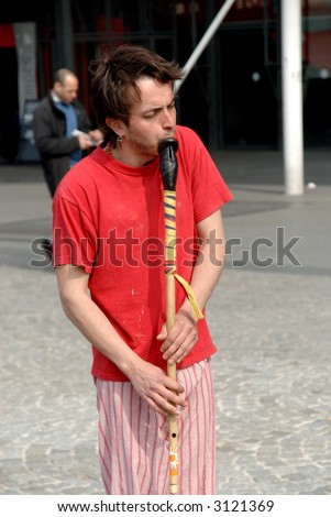 Male street performer, playing the flute in paris on place pompidou in france. focus on flute