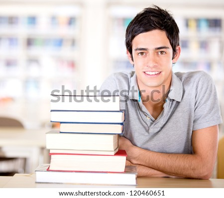Male student at the library with a pile of books