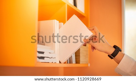 Male student hand choosing and picking off white book from orange bookshelf in college library for education research. Bestseller collection in bookstore. Scholarship and educational opportunity