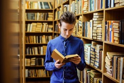 Male student in a blue shirt stands at the library and reads his favourite novel. One book in his hands, shelves with piles of books around him.