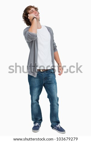 Male student laughing on the phone against white background - stock photo