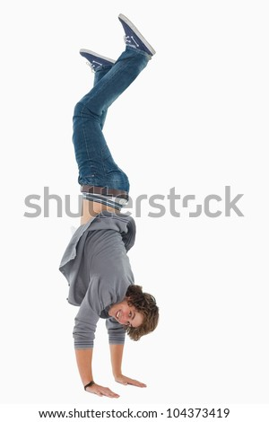 Male student posing handstands against white background