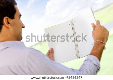 Male student reading a notebook outdoors - view from the back