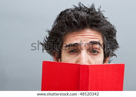 Male student reading a suspense novel - stock photo