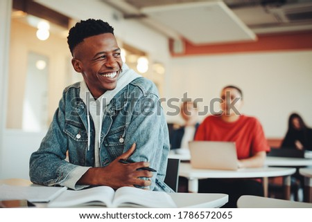 Male student sitting in university classroom looking away and smiling. Man sitting in lecture in high school classroom.