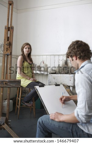 Male student sketching female model in art class #146679407
