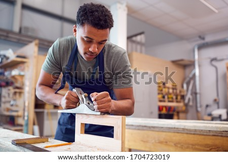 Male Student Studying For Carpentry Apprenticeship At College Using Wood Plane Photo stock ©