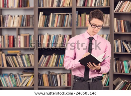 Male student uses to work through his subject material. Man student reading a book in the library of the institution. Male intern studying materials for their future profession. Buy in a bookstore.