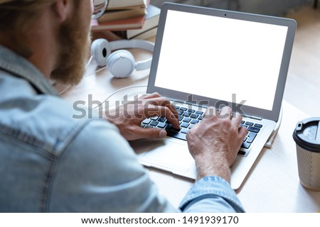 Male student using laptop software looking at empty white mock up computer screen learn easy internet course study online e learning in app type on notebook at table, over shoulder close up view