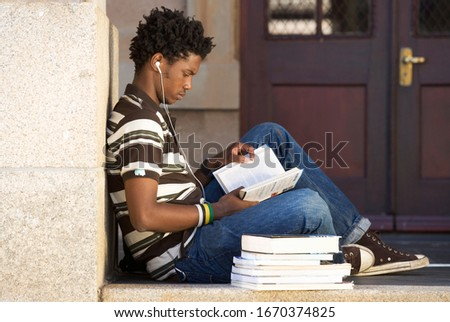 Male student wearing earphones studying books outside building