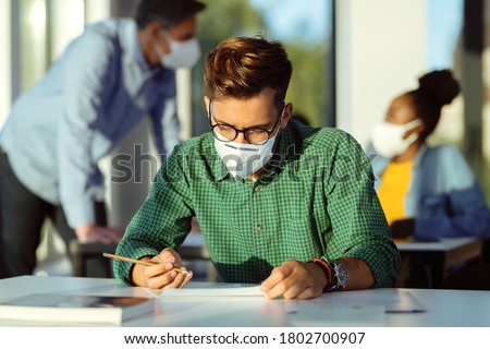 Male student wearing protective face mask while having an exam at lecture hall.