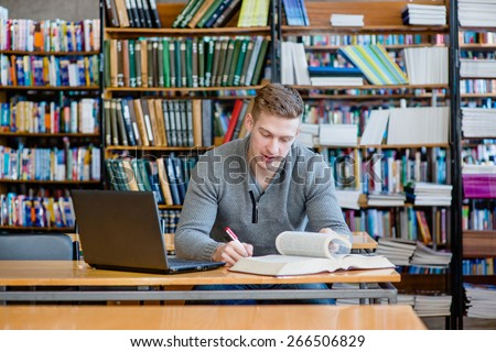Male student with laptop studying in the university library #266506829