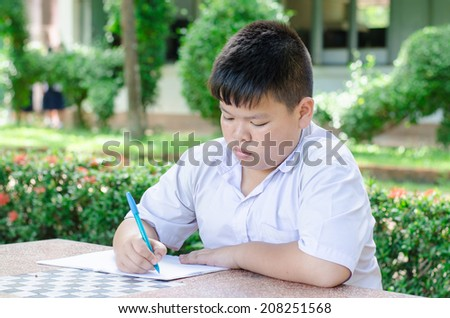Male Student Working At Desk In  School.