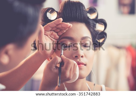 Male stylist creating  perfect smokey  eye make-up