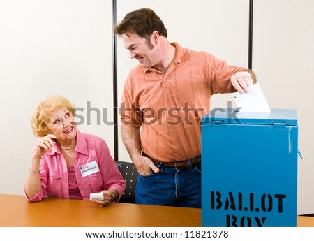 Male suburban voter casting his ballot while an election volunteer looks on. - stock photo