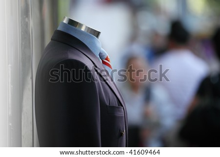 Male suit in street on display, people walking by. Shallow DOF.