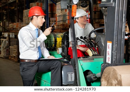 Male supervisor with clipboard instructing forklift driver at warehouse