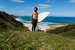 Male surfer on beach walking trail path with surf board looking sea waves from cliff, wearing wet suit at paradise nature surfing reserve, beautiful Guarda do Embau, famous summer travel destination