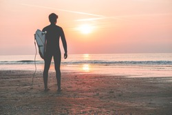 Male surfer standing on the beach waiting for waves at sunset time - Man with surfboard wearing wet suit looking the waves - Extreme sport concept