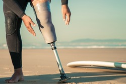 Male surfer wearing wetsuit for, adjusting artificial limb taped to leg. Cropped shot. Artificial limb and active lifestyle concept