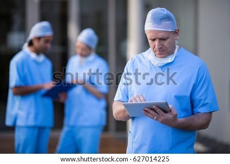 Male surgeon using digital tablet at hospital