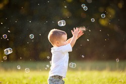 Male sweet kid in nature reaching soap bubbles