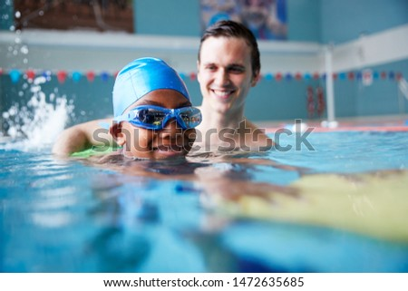 Male Swimming Coach Giving Boy Holding Float One To One Lesson In Pool Stockfoto ©