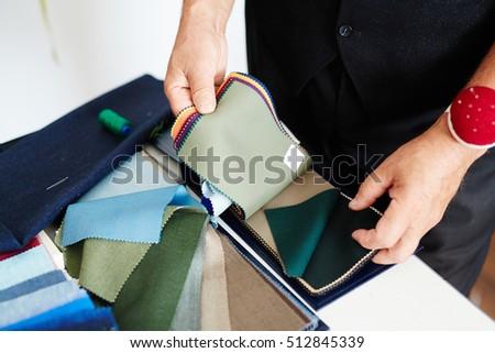 Male tailor choosing fabric