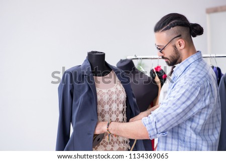 Male tailor working in the workshop on new designs #1134369065