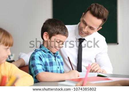 male teacher helping boy with...