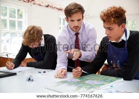 Male Teacher Helping Teenage Pupils In Art Class