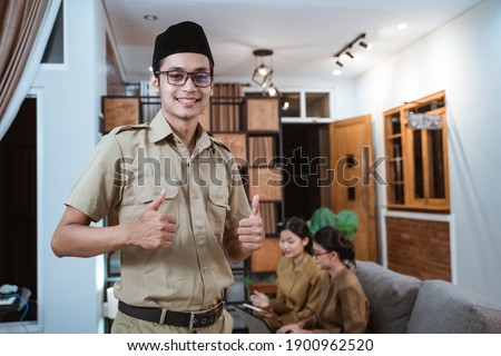male teacher in civil servant uniform smiling looking at the camera with a thumbs up while working with the team from home